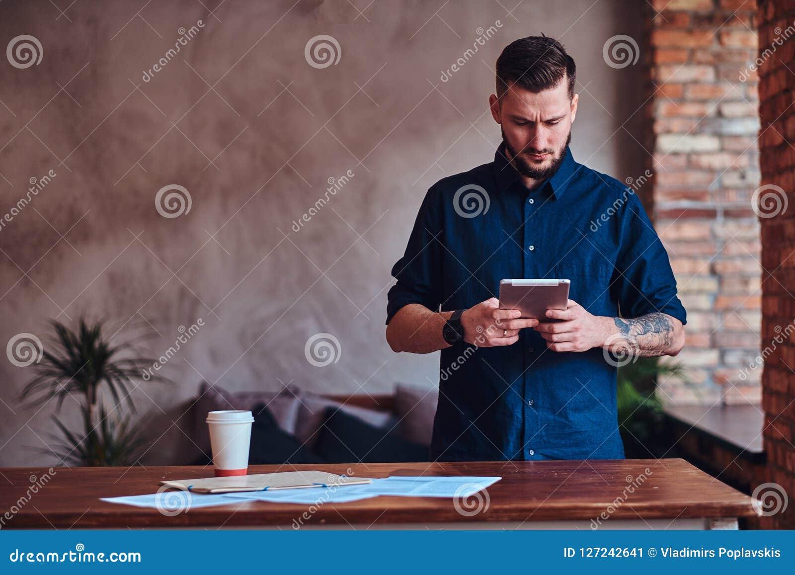 Uomo barbuto bello che lavora con la compressa in ufficio con l interno del sottotetto