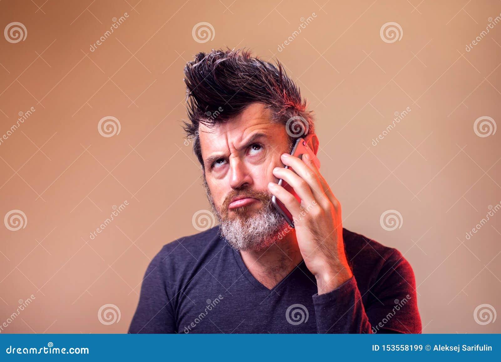 Uomo barbuto che pensa e che cerca mentre avendo una chiacchierata sul suo Smart Phone La gente, emozioni, concetto di tecnologia