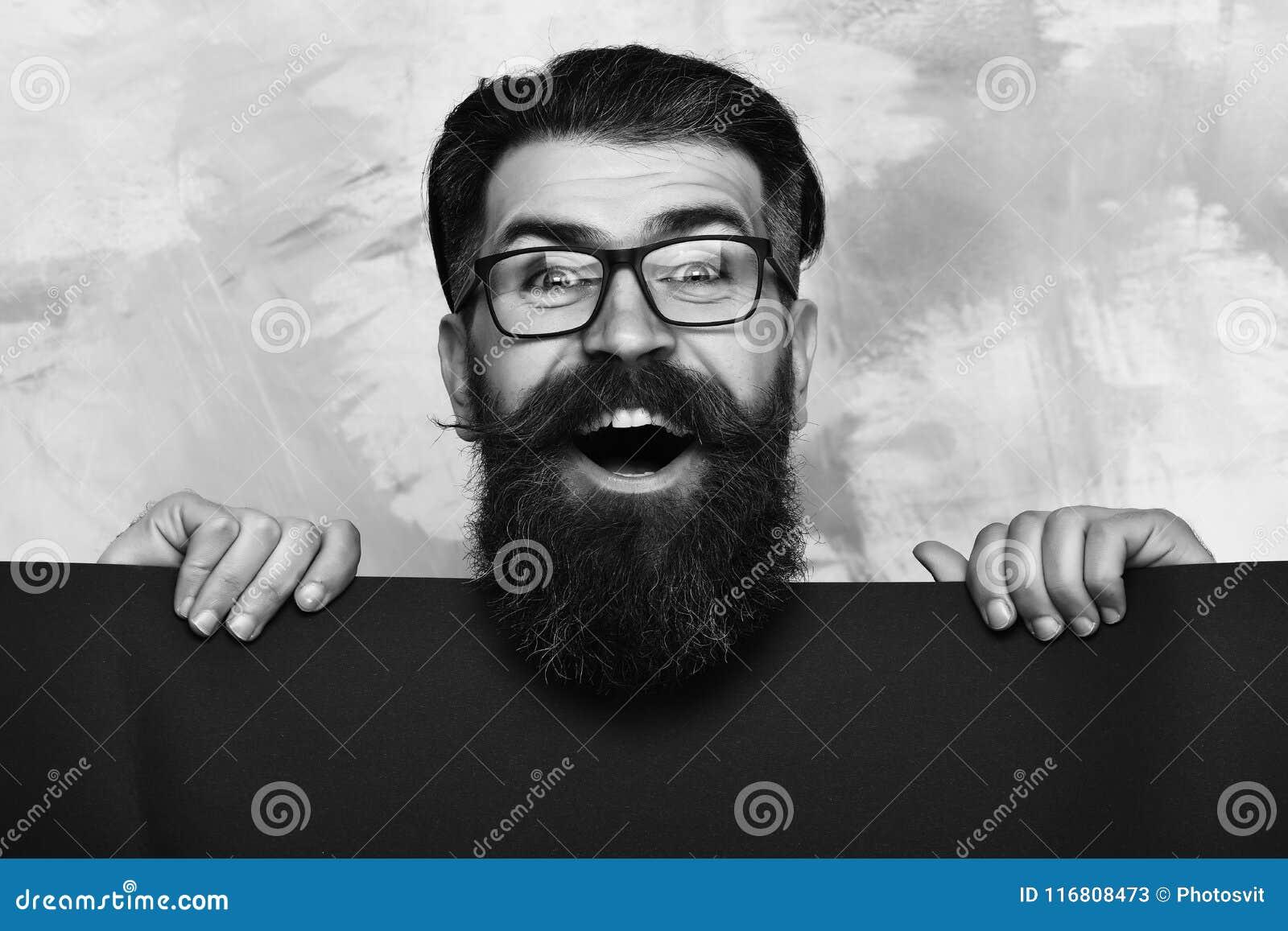 Uomo barbuto con il fronte felice in vetri su fondo variopinto