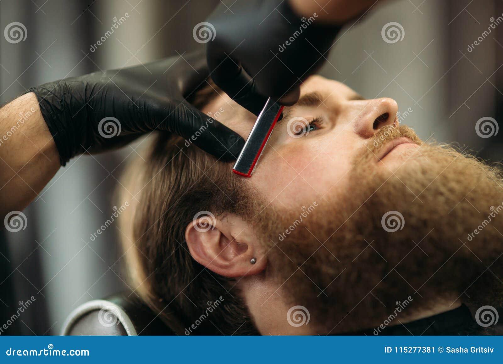 Uomo barbuto con la barba lunga che ottiene capelli alla moda che si radono, taglio di capelli, con il rasoio dal barbiere in par