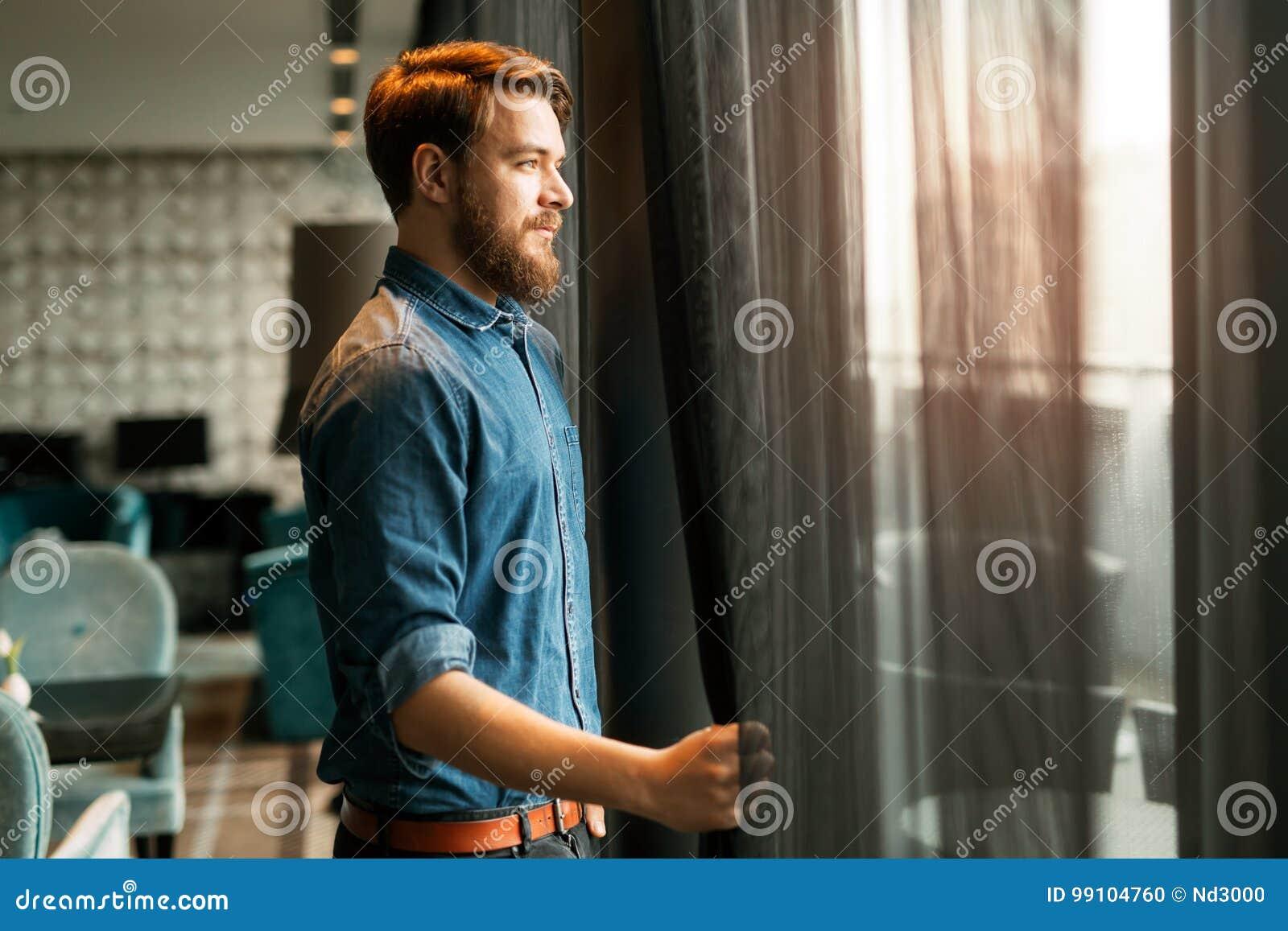 Uomo bello che esamina paesaggio urbano