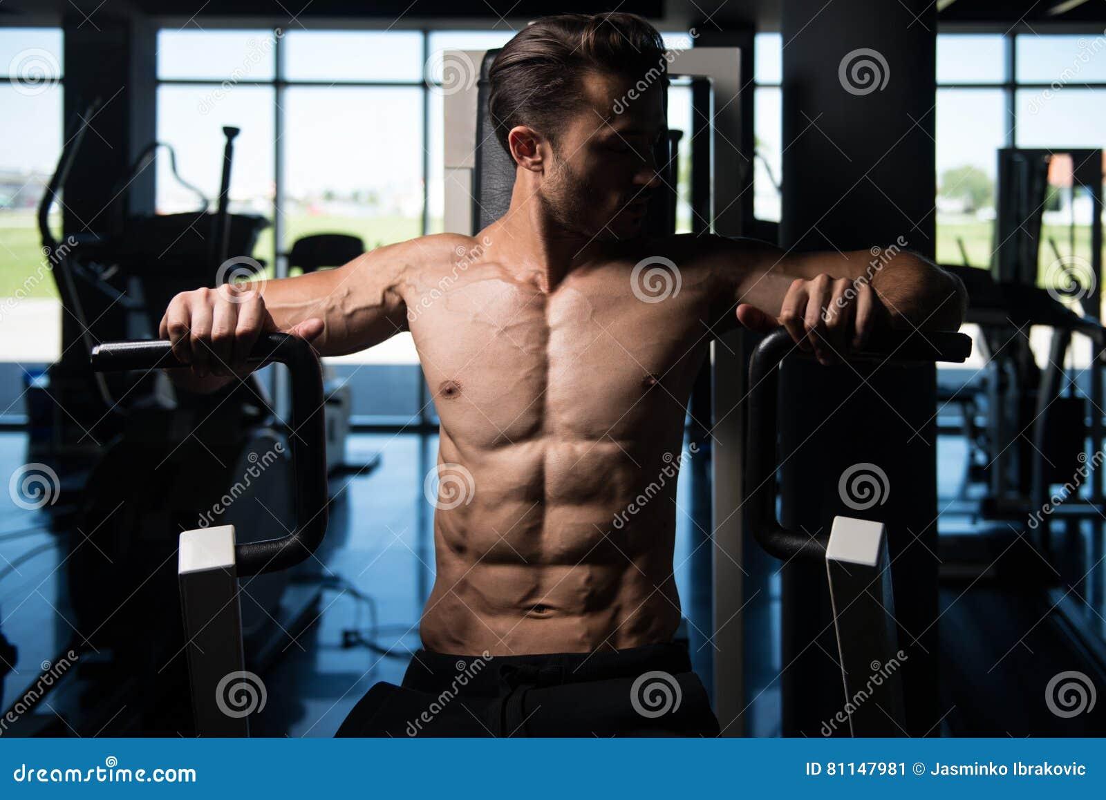 Uomo bello che fa esercizio pesante per il petto