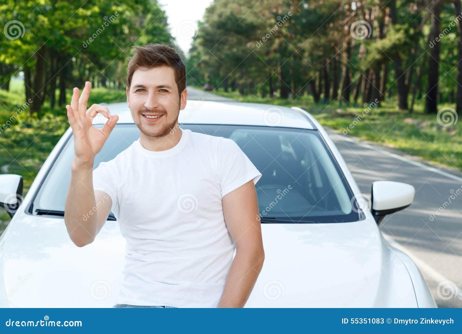 Uomo bello che indica automobile vicina giusta