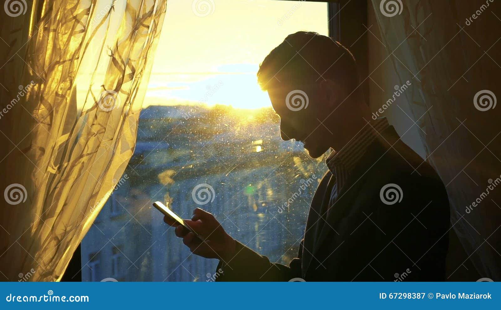 Uomo Bello Che Per Mezzo Del Telefono Sorridente Contro Lo Sfondo
