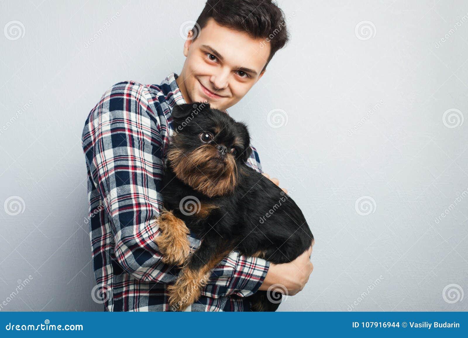 Uomo bello dei pantaloni a vita bassa del ritratto del primo piano il giovane, baciante il suo cane nero del buon amico ha isolat
