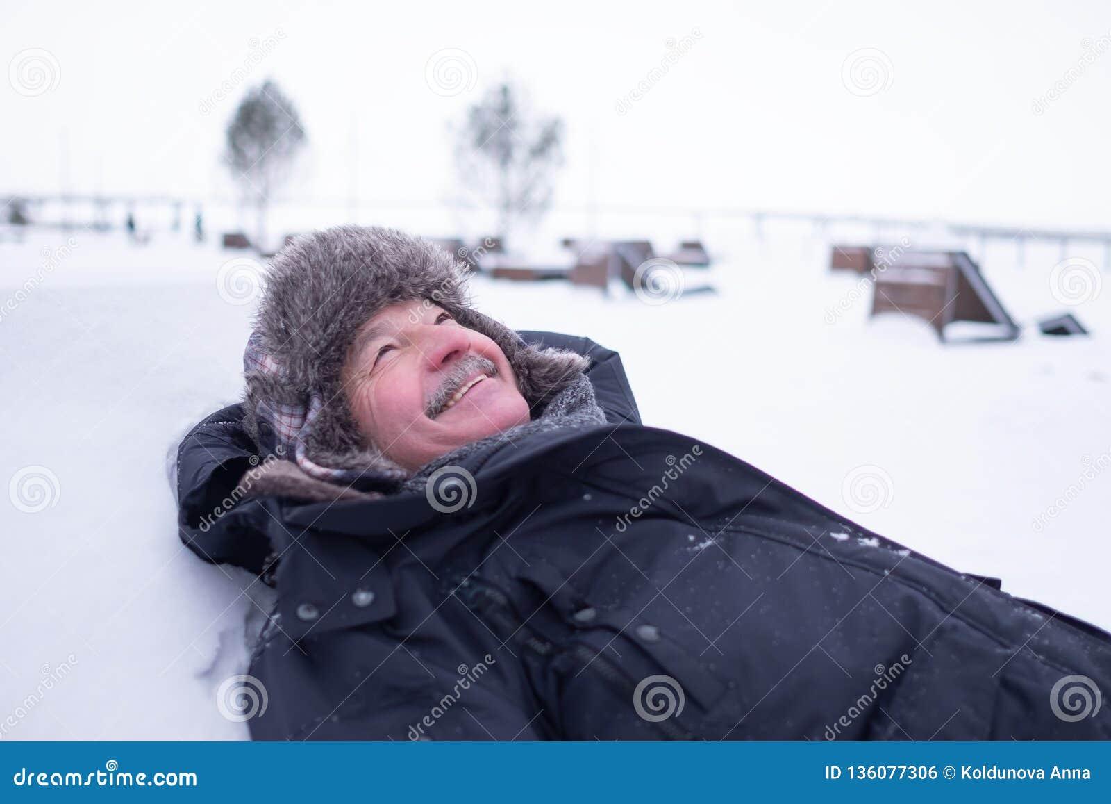 Uomo bello senior in vestiti caldi e cappello che si trovano sulla neve e sul sogno