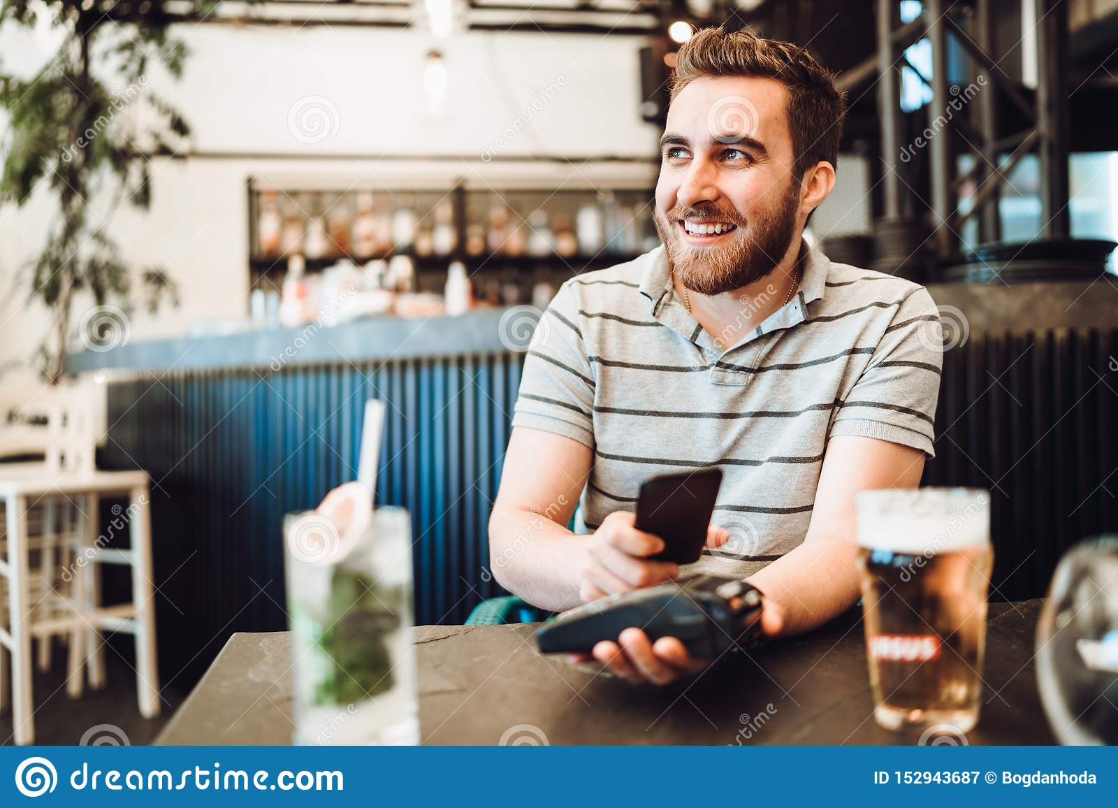 Uomo bello sorridente che paga al ristorante facendo uso della tecnologia mobile di paga, sistema di pagamento moderno del nfc