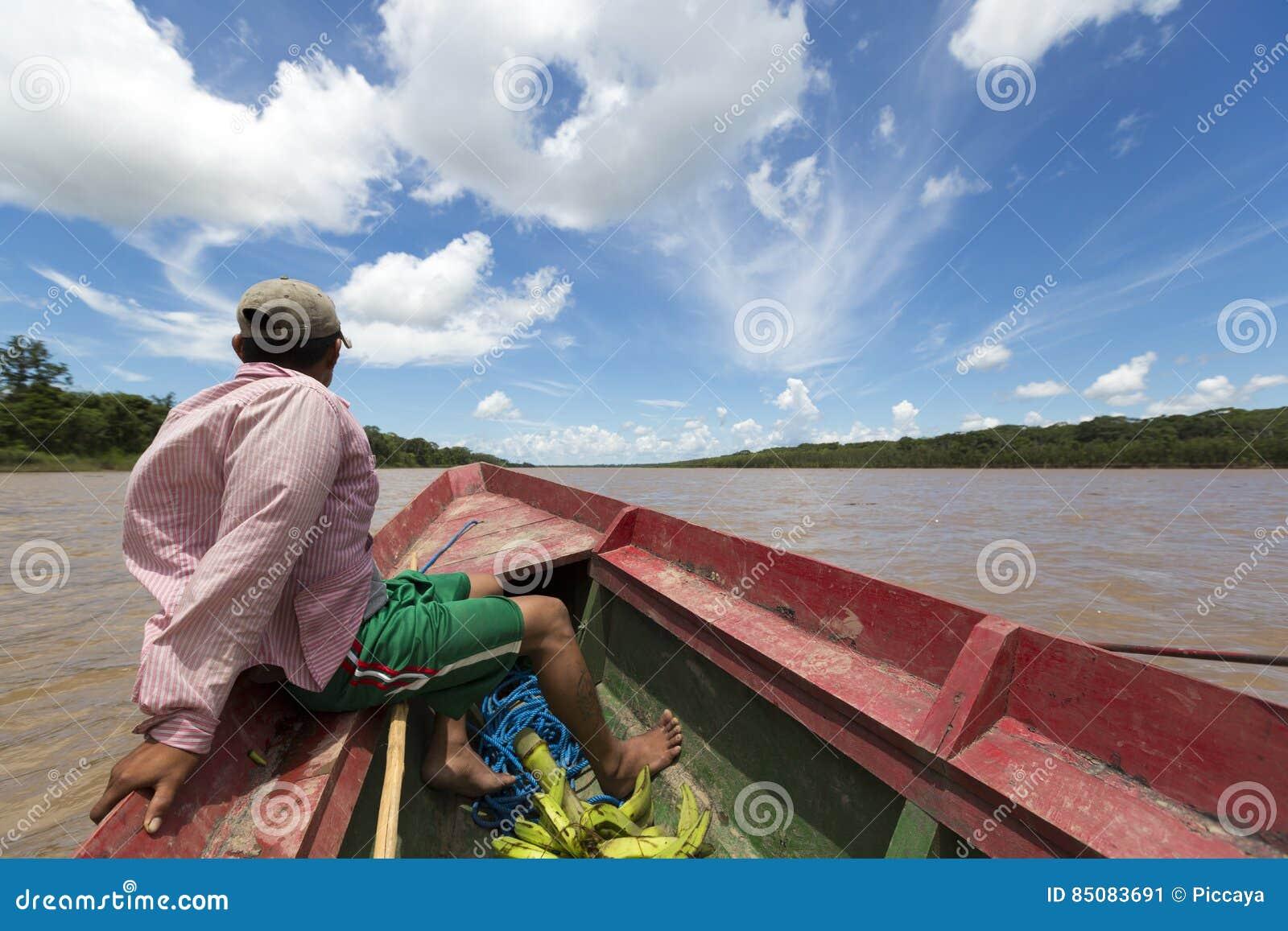 Uomo boliviano locale che viaggia su una barca di legno sul fiume di Beni, Ru