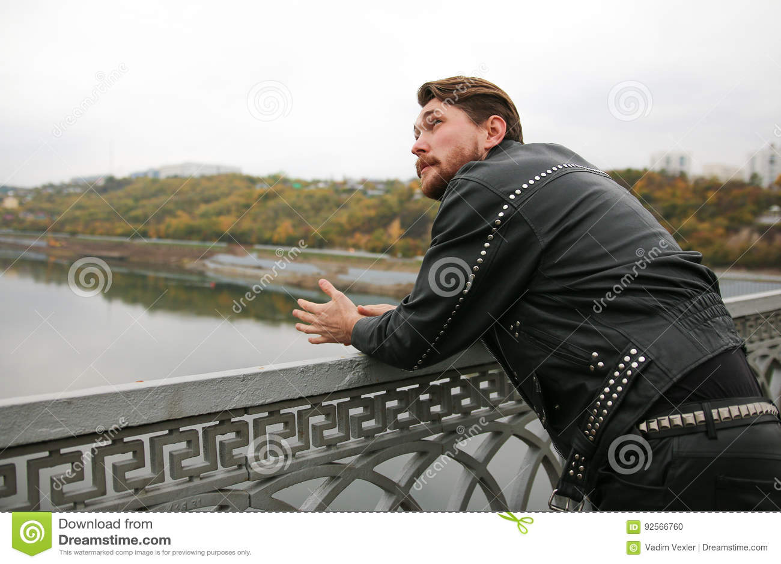 Uomo in bomber neri che esaminano fiume