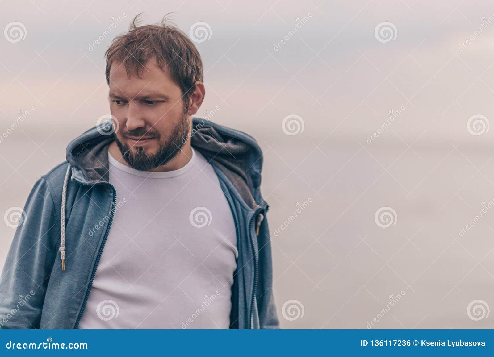Uomo brutale con una barba contro lo sfondo di un cielo e di un mare vuoti