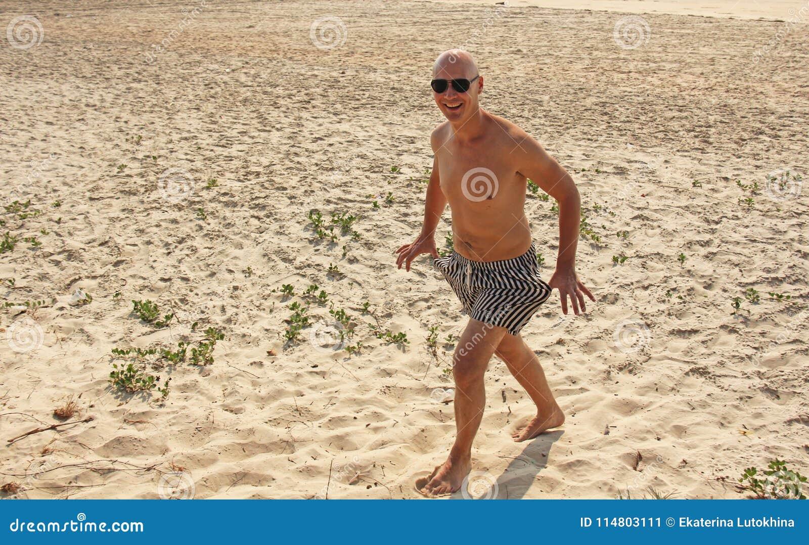 e0f0af8fbad2 Uomo calvo con un petto nudo nudo, in costume da bagno a strisce o negli  shorts contro lo sfondo della spiaggia e del mare, in occhiali da sole neri  Da solo ...