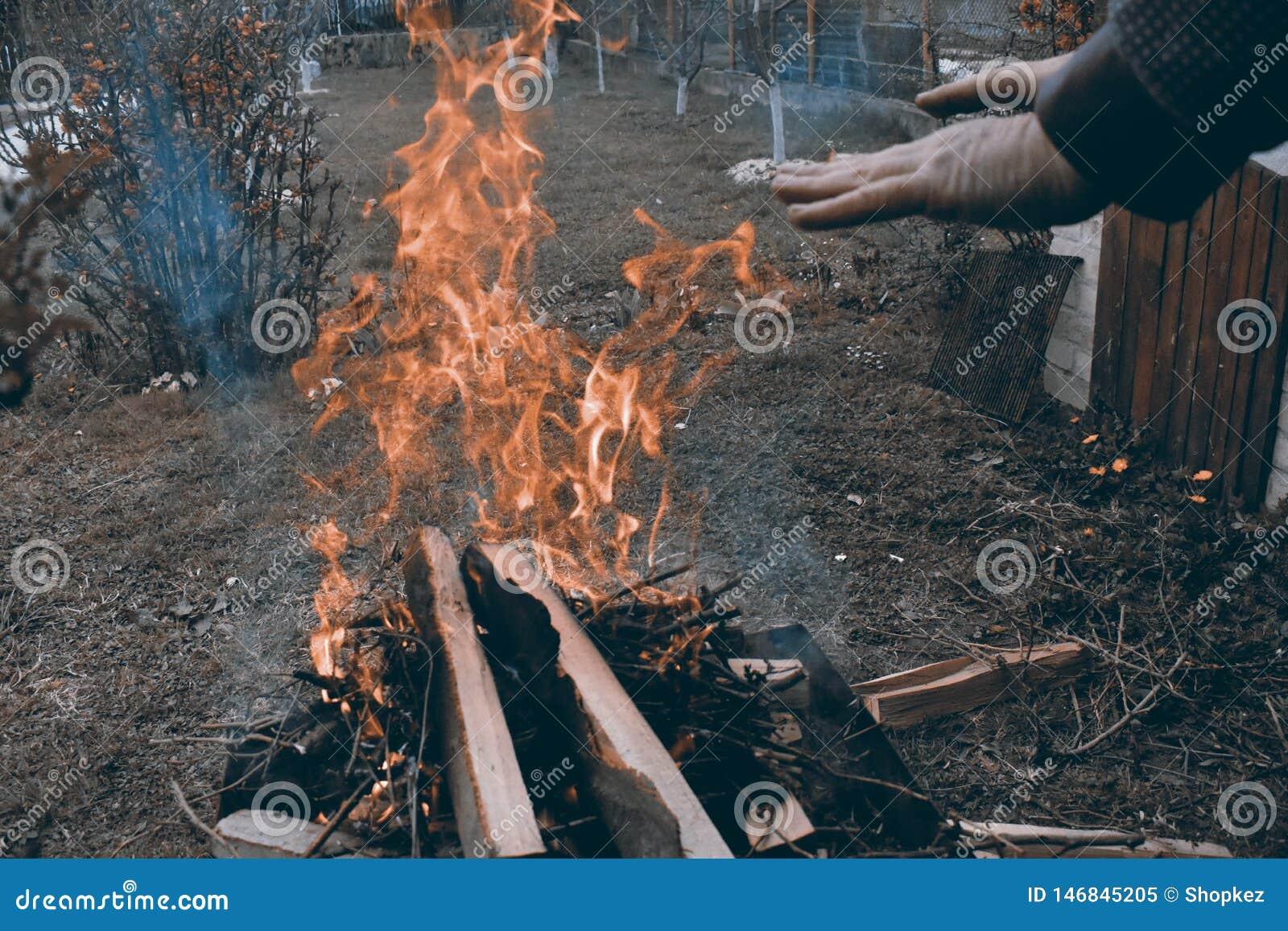 Uomo caucasico che riscalda le sue mani al fuoco di accampamento in un atmosfera scura fredda