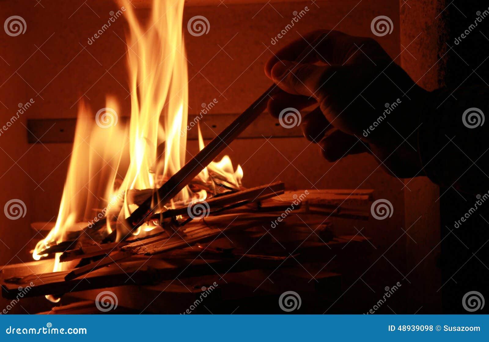 Uomo che accende il fuoco del camino fotografia stock immagine