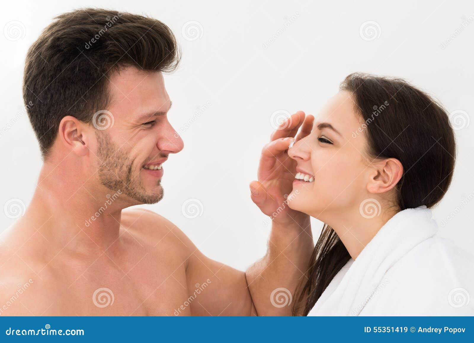 Uomo che applica idratante sul naso della donna