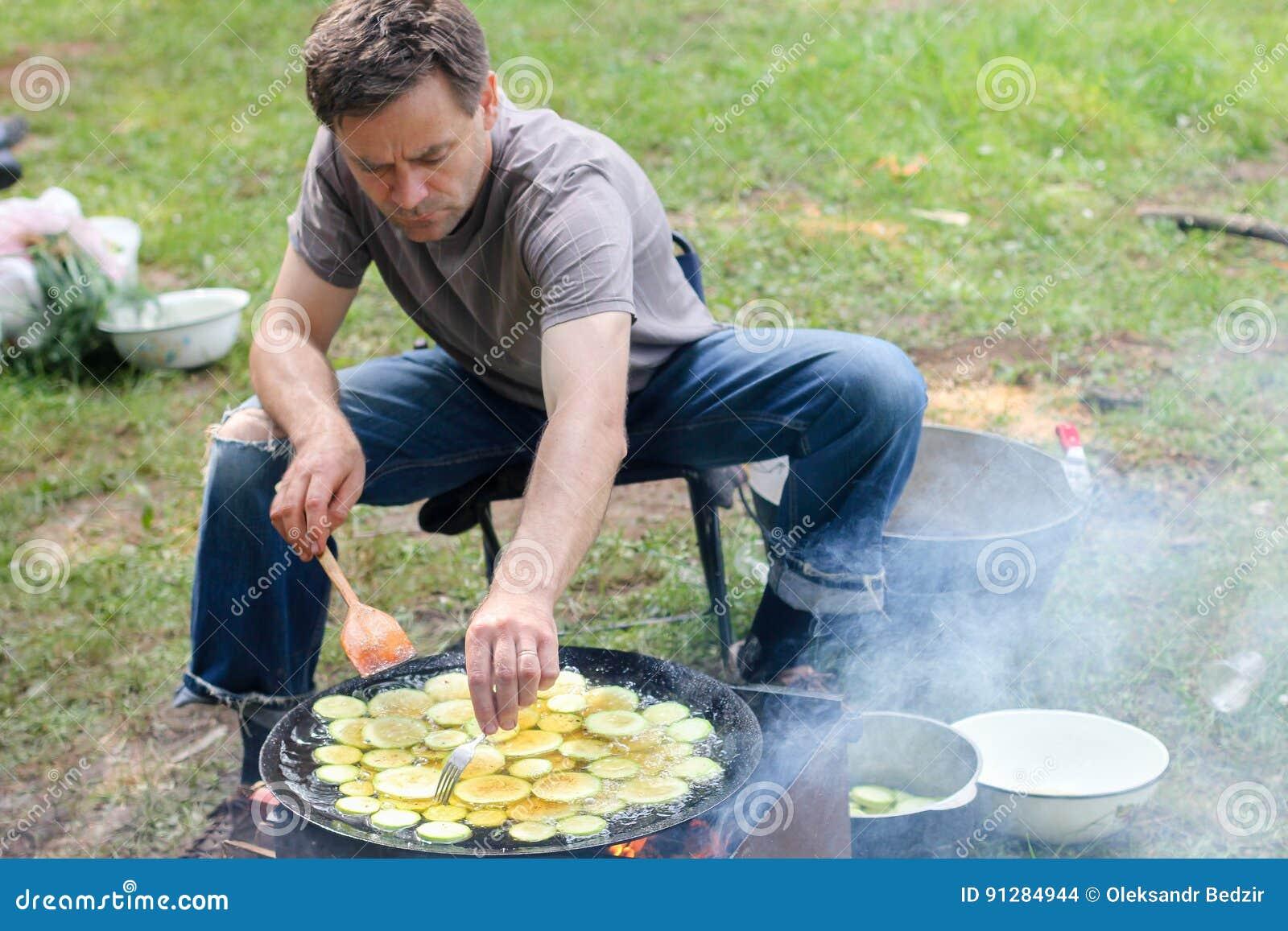 Uomo che cucina carne sopra il falò al campeggio