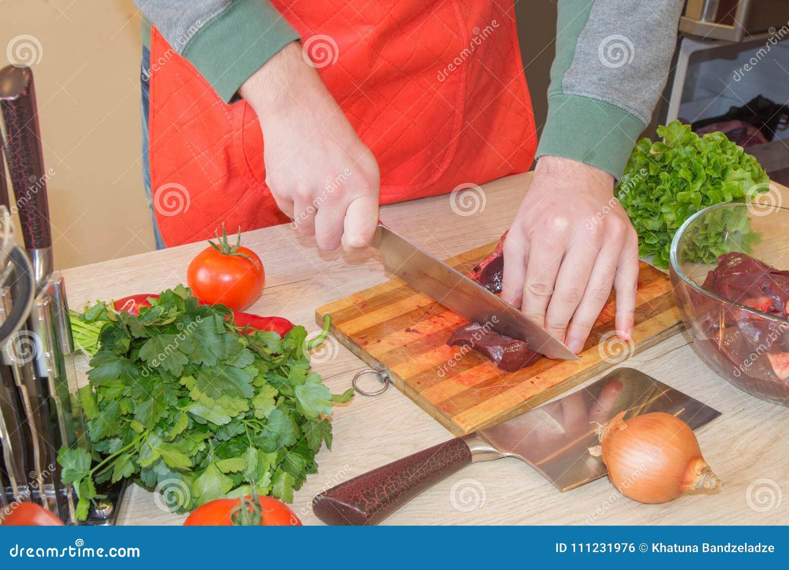 Uomo che cucina pasto nella cucina Giovane carne maschio di taglio del cuoco unico sul bordo di legno