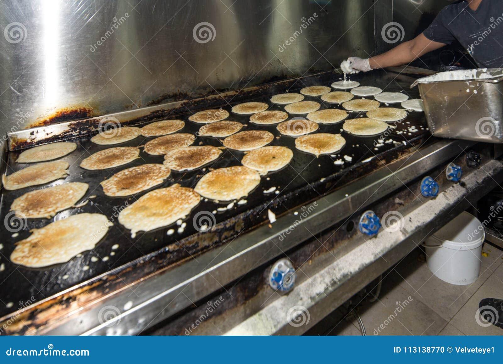 Uomo che cucina in un industriale & in un Comme sporchi Grungy reali del ristorante
