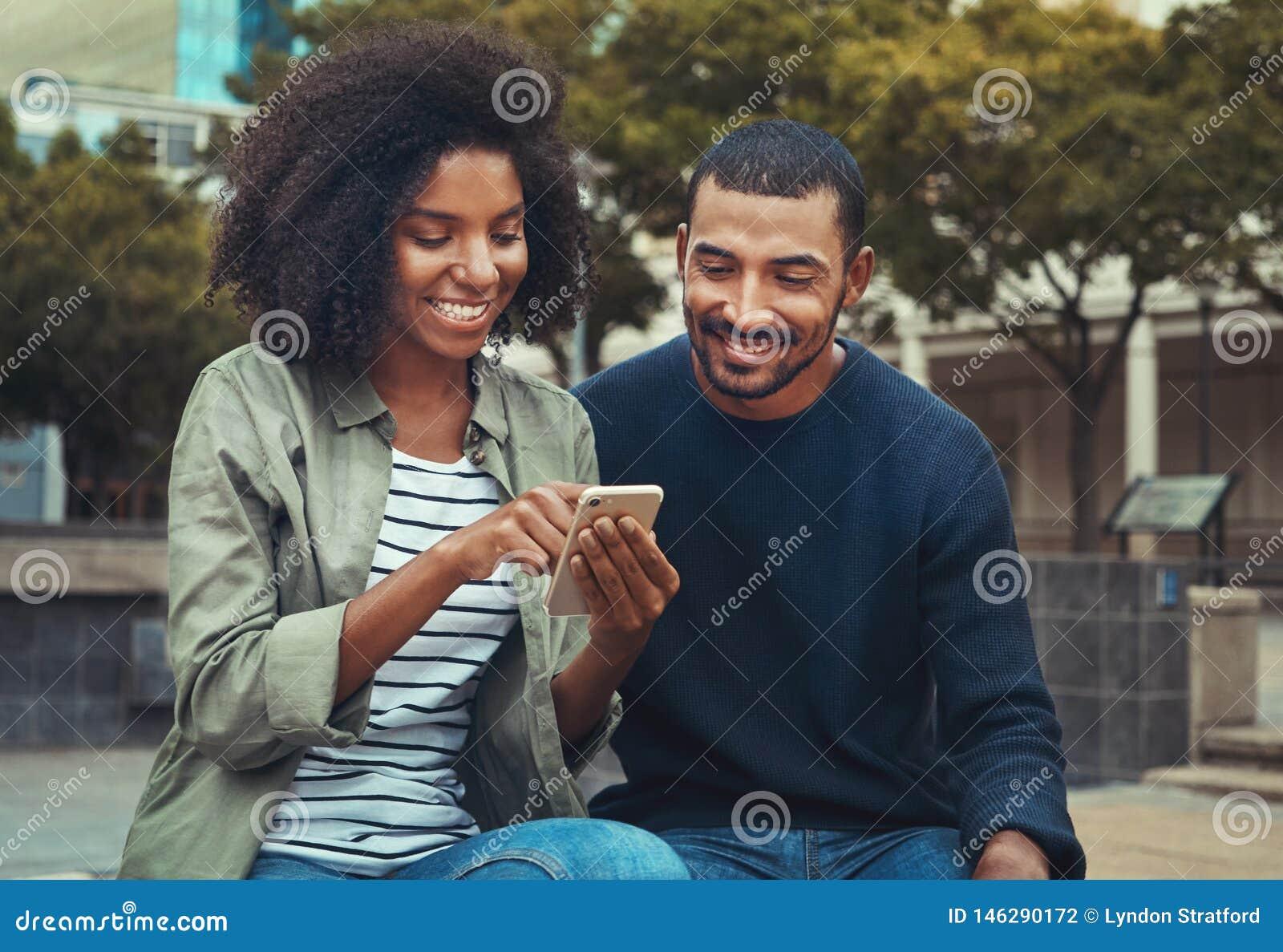 Uomo che esamina la sua amica che per mezzo del telefono cellulare