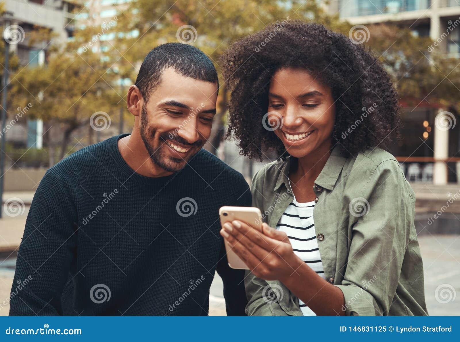 Uomo che esamina telefono cellulare tenuto dalla sua amica