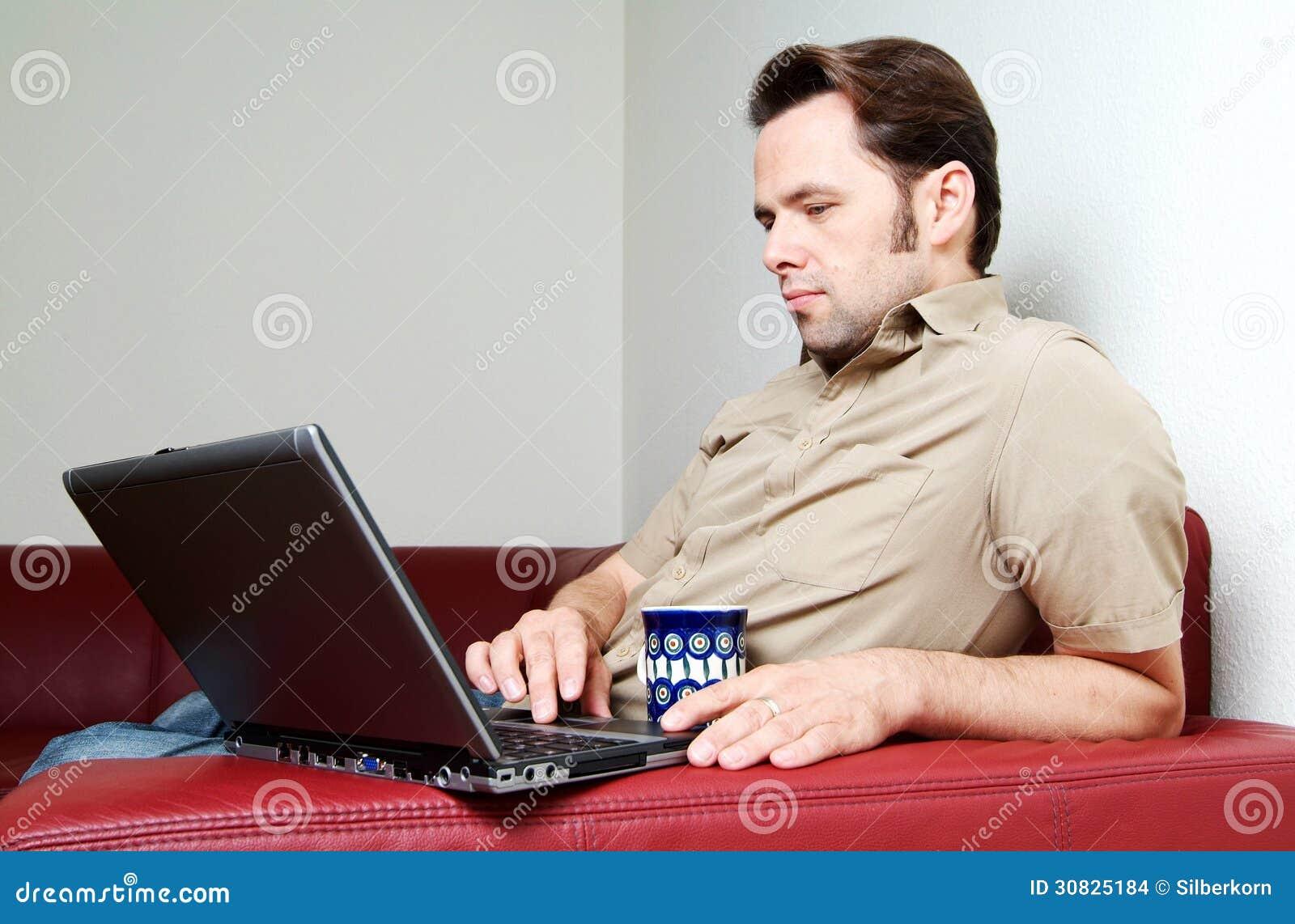 Uomo che fa un certo worh del computer portatile a casa