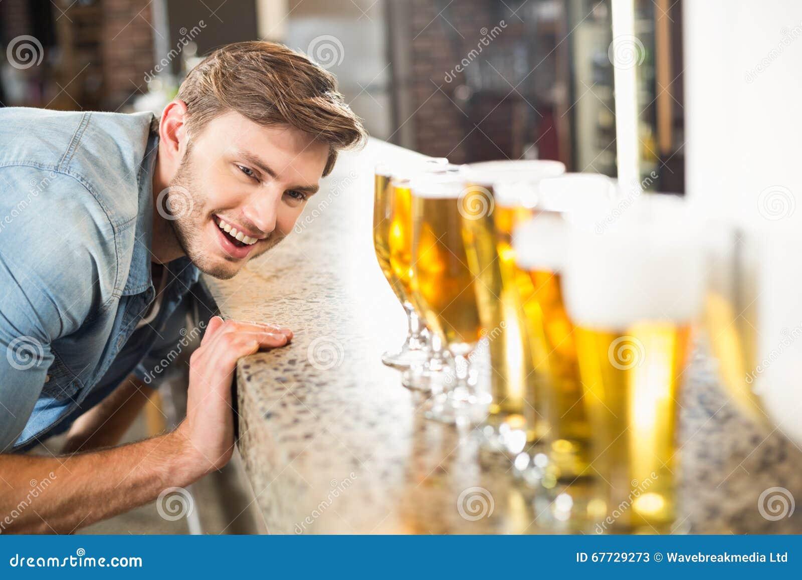 Uomo che guarda giù le birre allineate