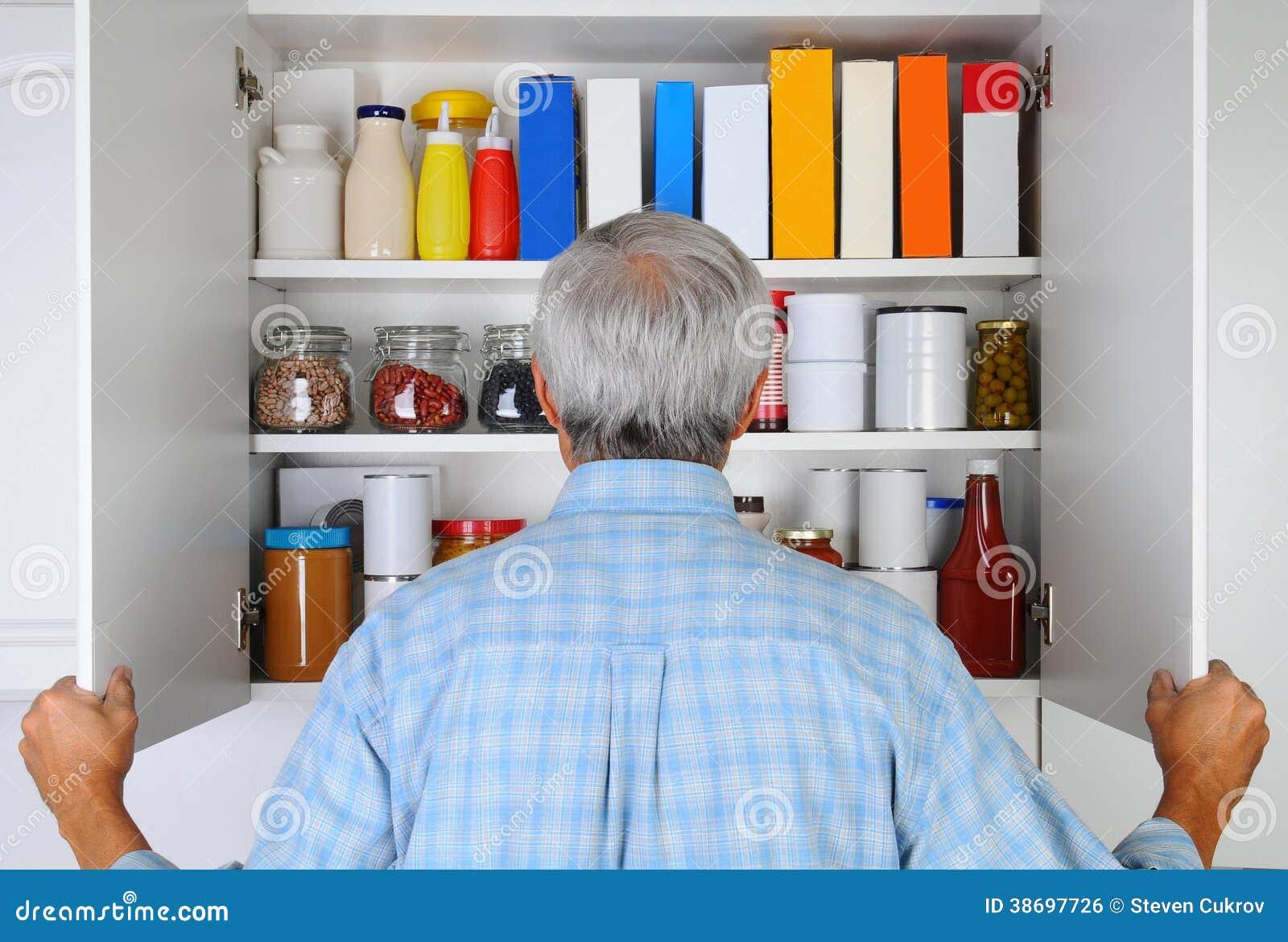 Uomo che guarda nella sua dispensa