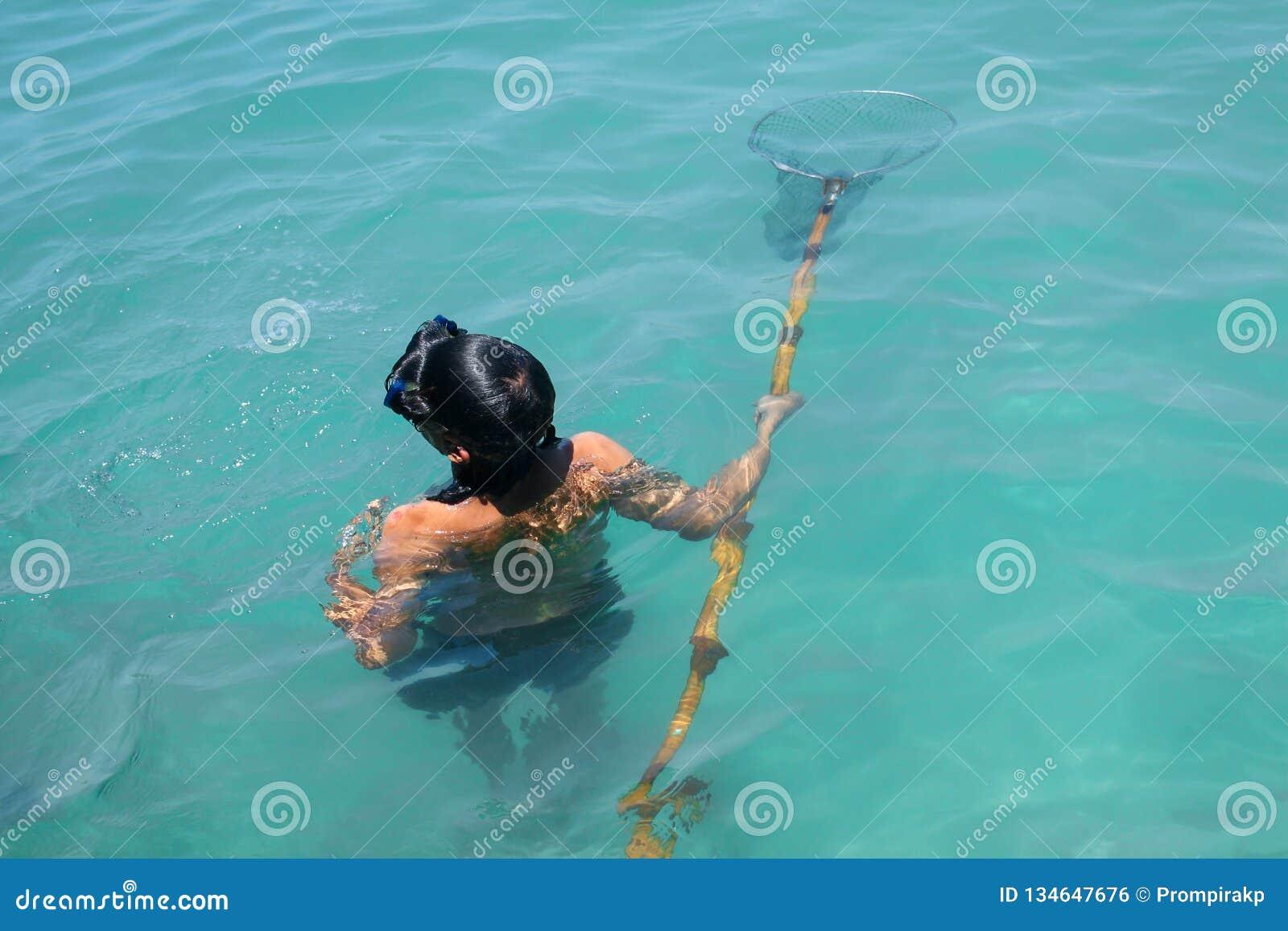 Uomo che guida nell ambito del ritrovamento dell acqua e che cerca animale acquatico nel mare