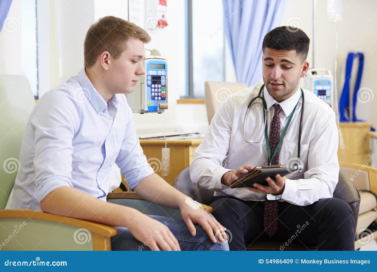 Uomo che ha chemioterapia con il dottore Using Digital Tablet