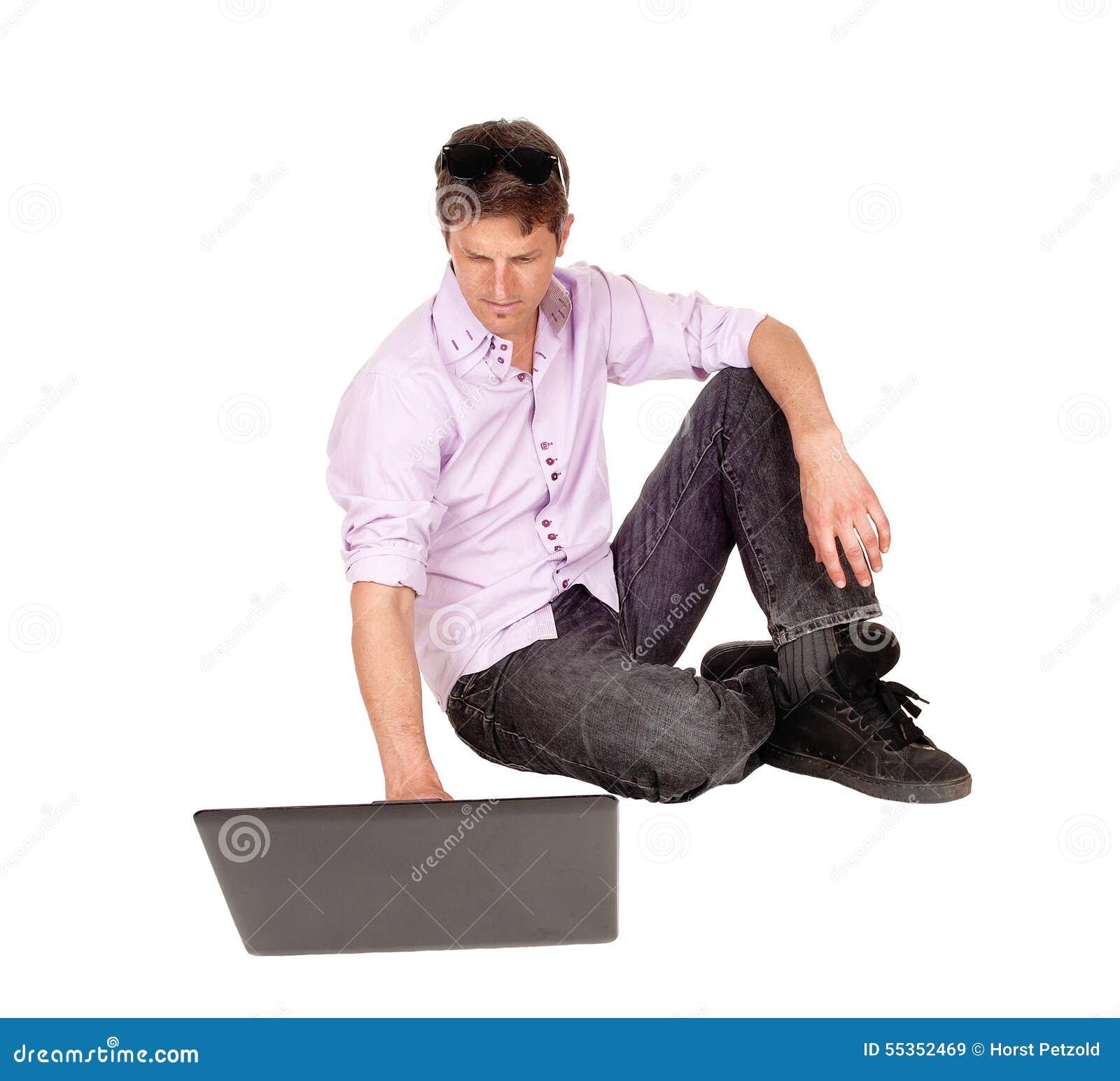 Uomo che lavora al computer portatile del pavimento