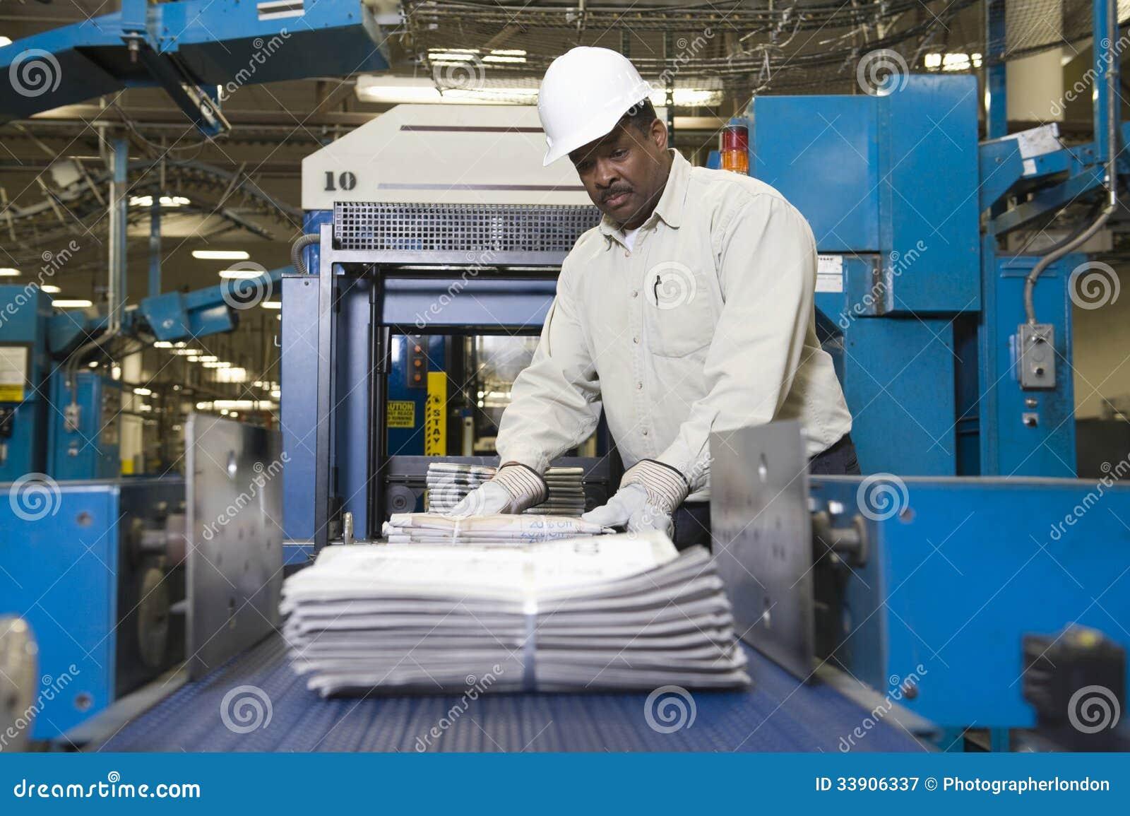 Uomo che lavora alla linea di produzione del giornale