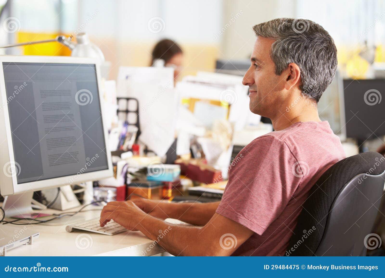 Uomo che lavora allo scrittorio in ufficio creativo occupato