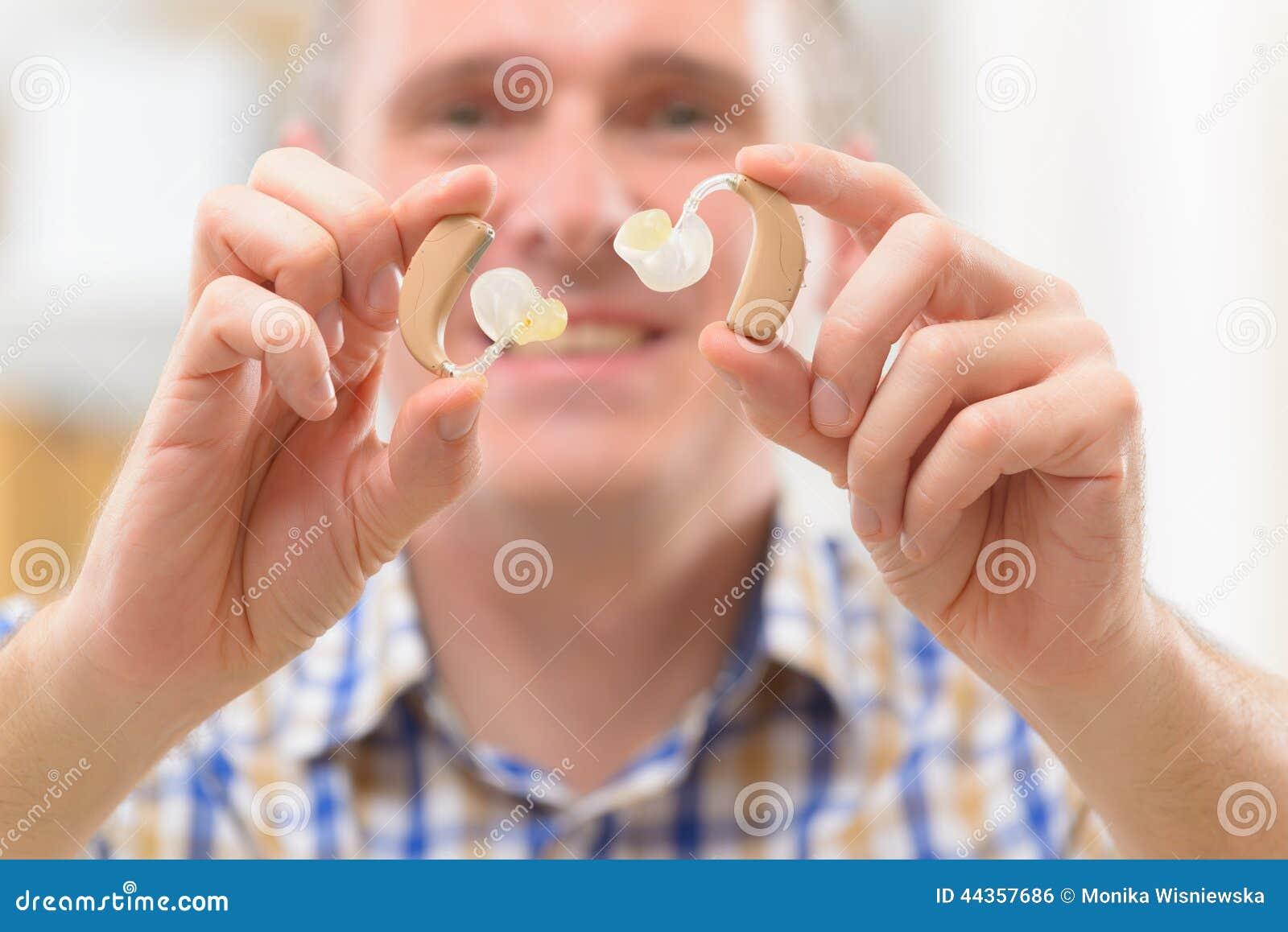 Uomo che mostra gli aiuti sordi