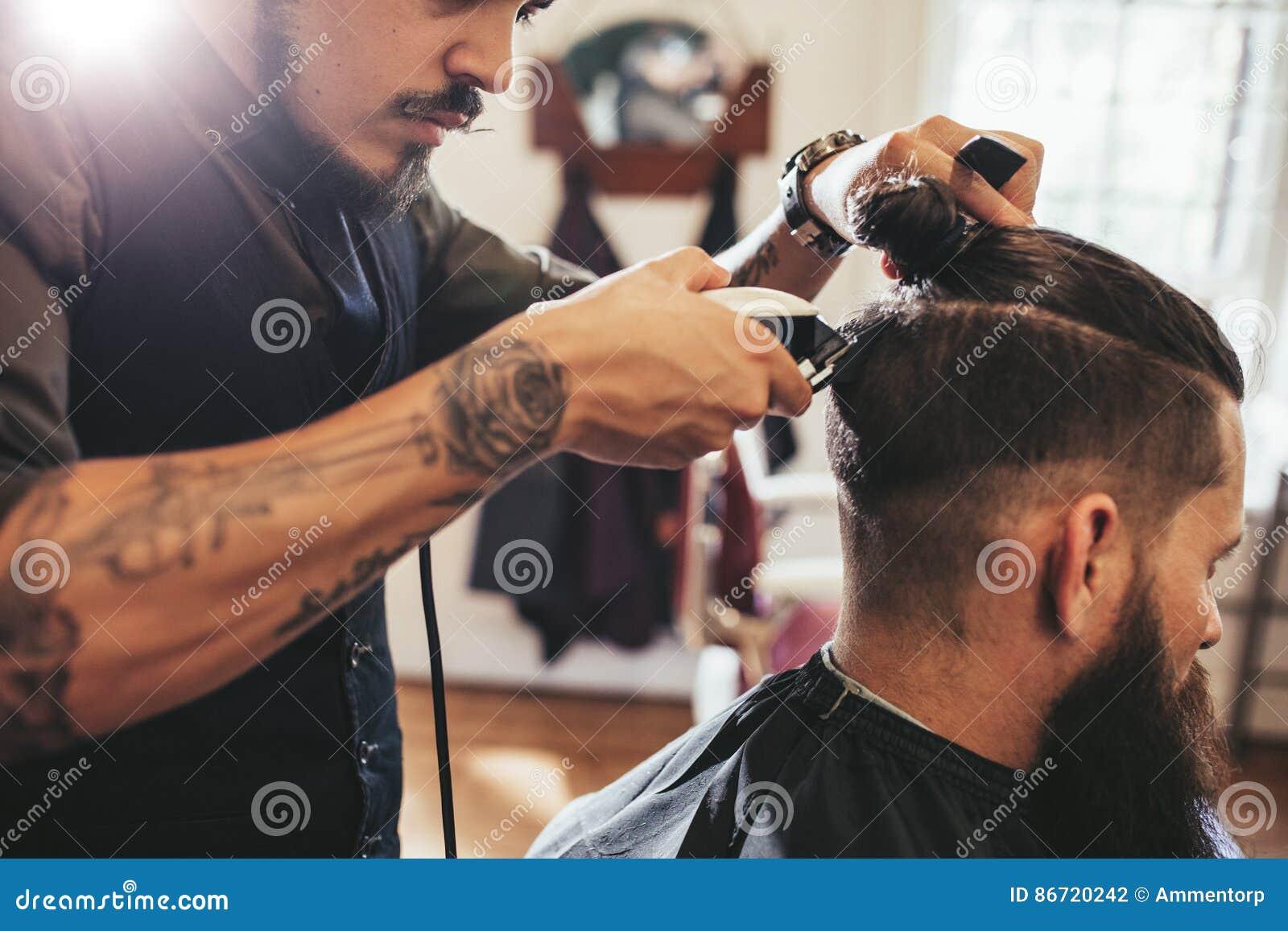 Uomo che ottiene taglio di capelli d avanguardia nel negozio di barbiere