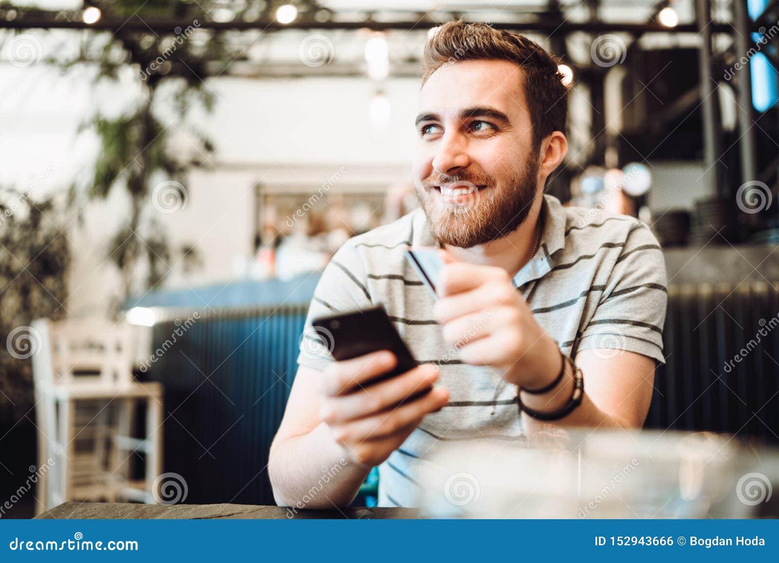 Uomo che paga facendo uso della carta di credito e del telefono cellulare Concetto di sistemi moderno di pagamento