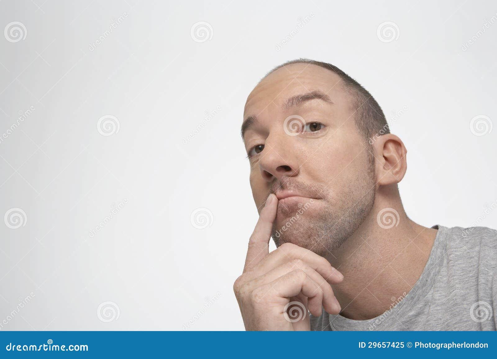 Uomo che pensa con il dito sulle labbra