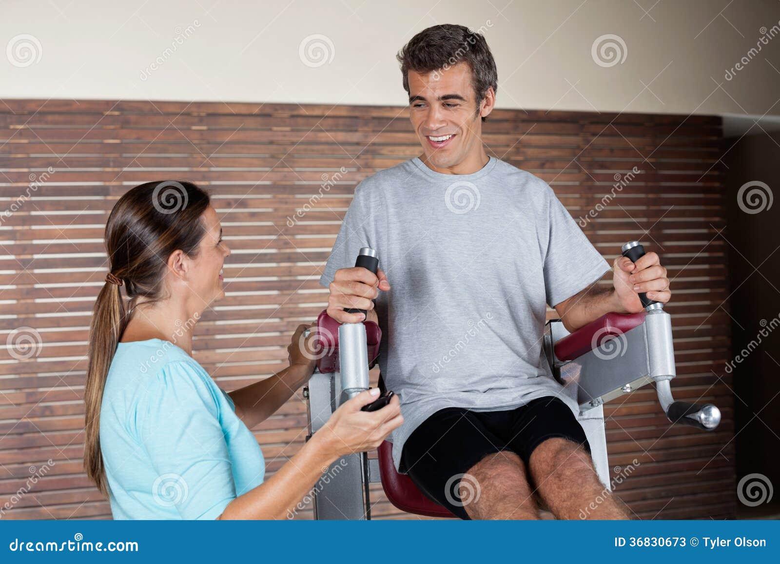 Uomo che per mezzo di una macchina di esercizio mentre esaminando