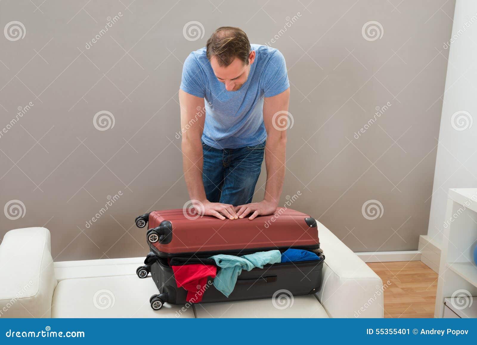 Uomo che prova a chiudere valigia