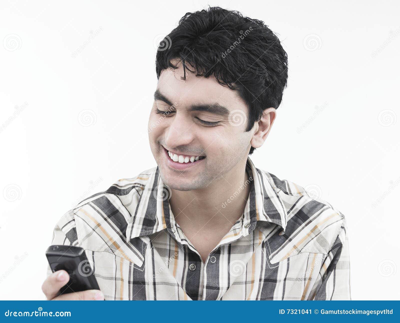 Uomo che ride del suo telefono delle cellule