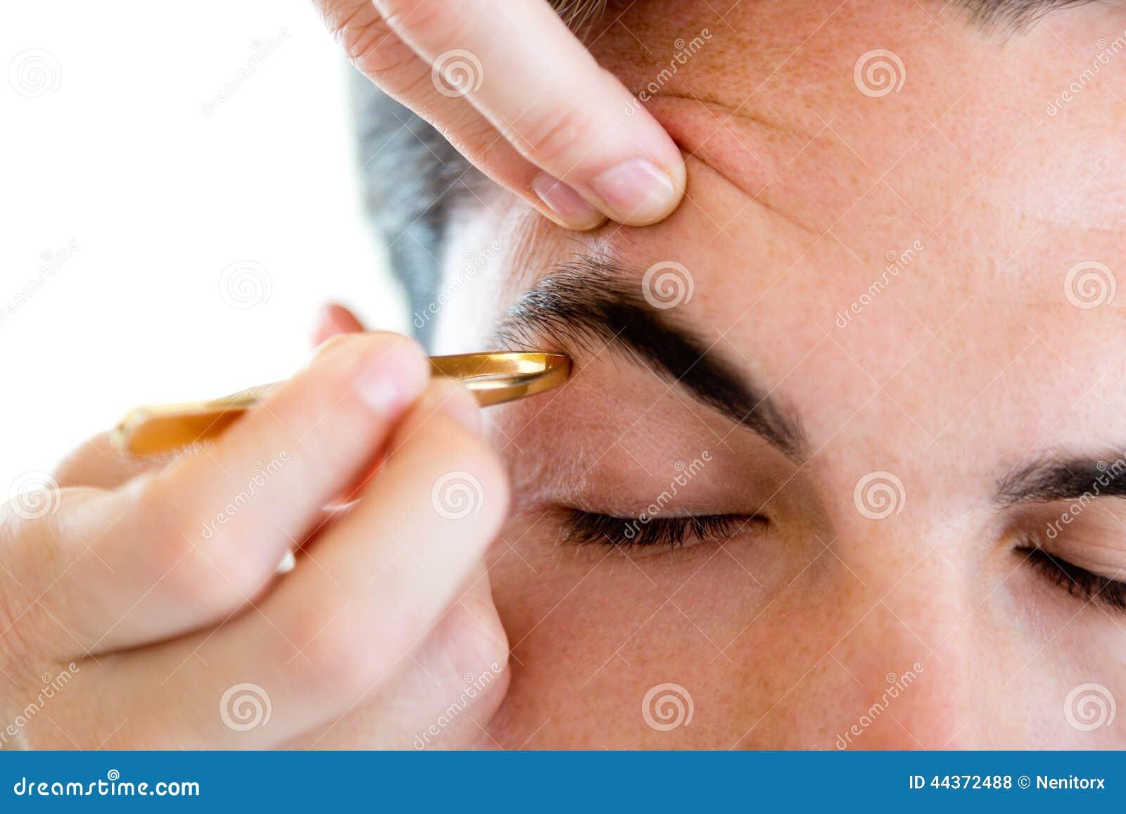 Uomo che rimuove i capelli del sopracciglio con depilare