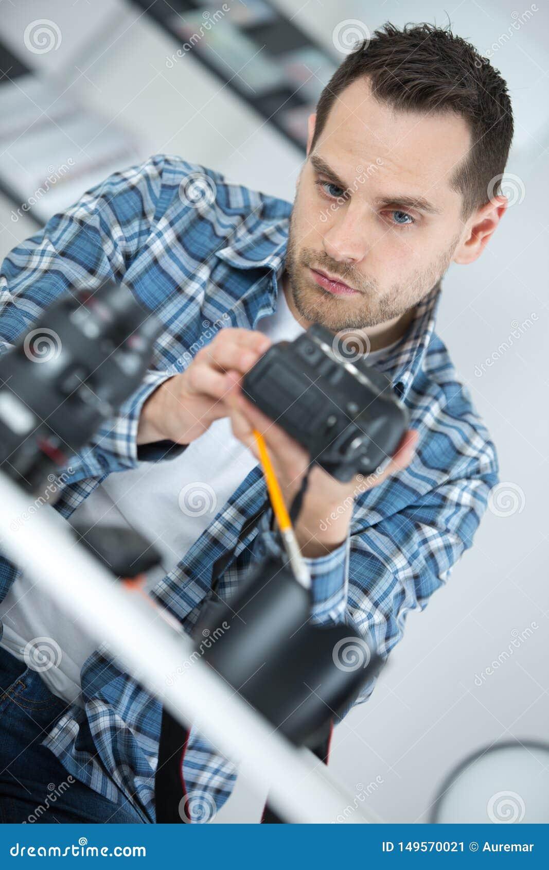 Uomo che ripara una macchina fotografica