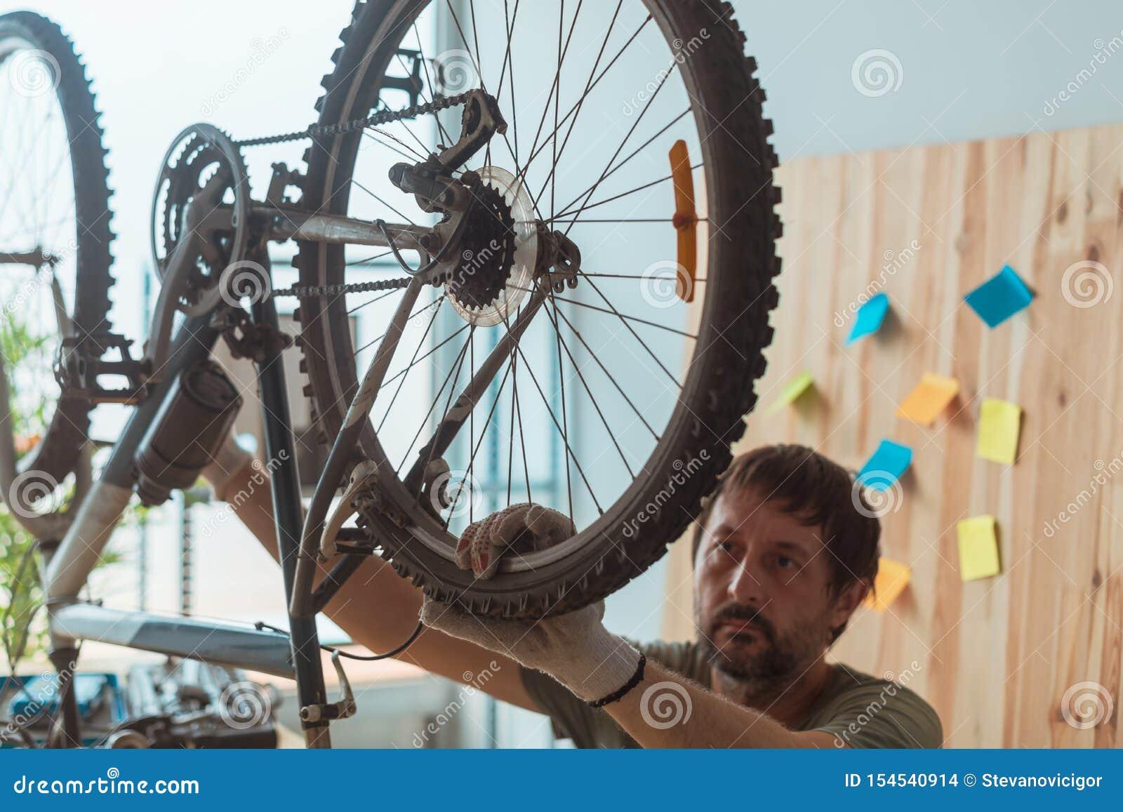 Uomo che ripara vecchio mountain bike in officina