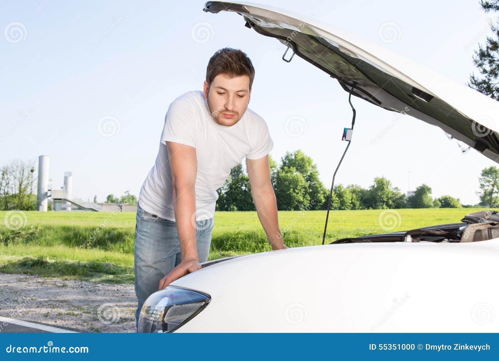 Uomo che si appoggia automobile con il cofano aperto