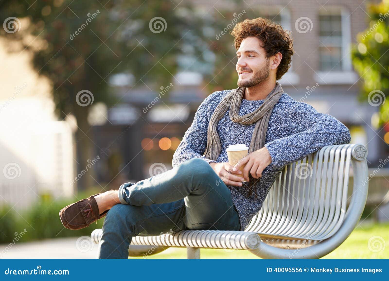 Uomo che si rilassa sul banco di parco con caffè asportabile