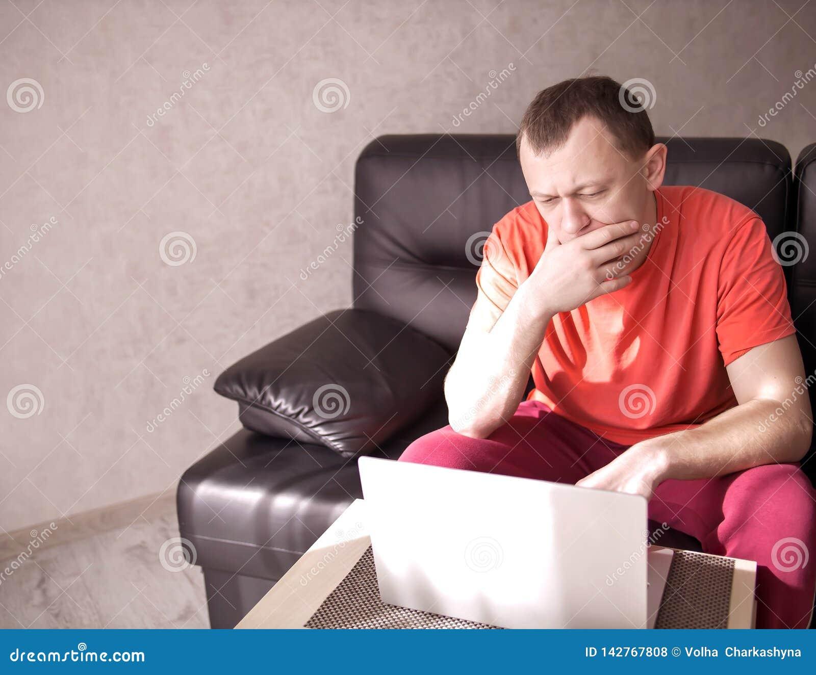 Uomo che si siede sullo strato e che lavora al suo computer portatile, copyspace