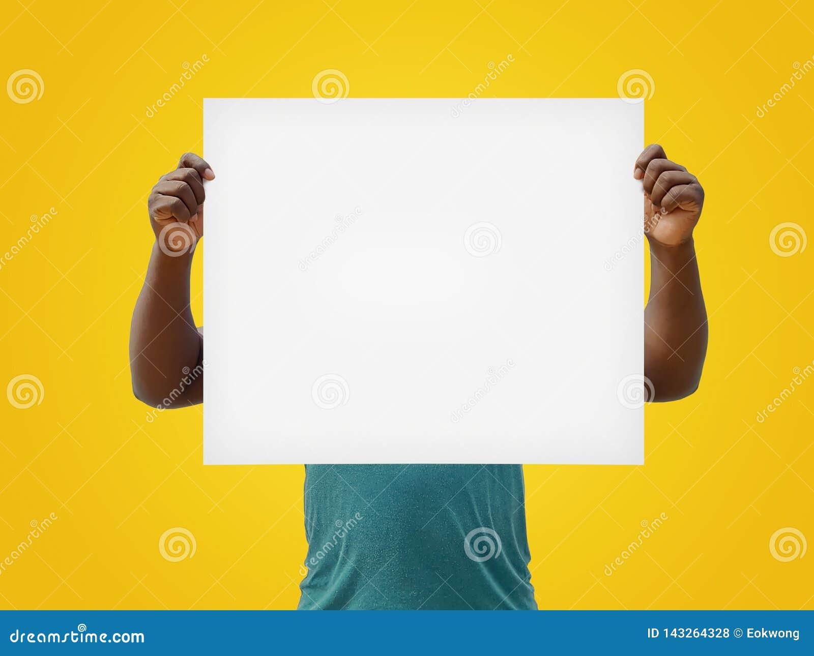 Uomo che tiene un bianco in bianco per cedere firmando un documento il suo fronte, isolato su un fondo giallo