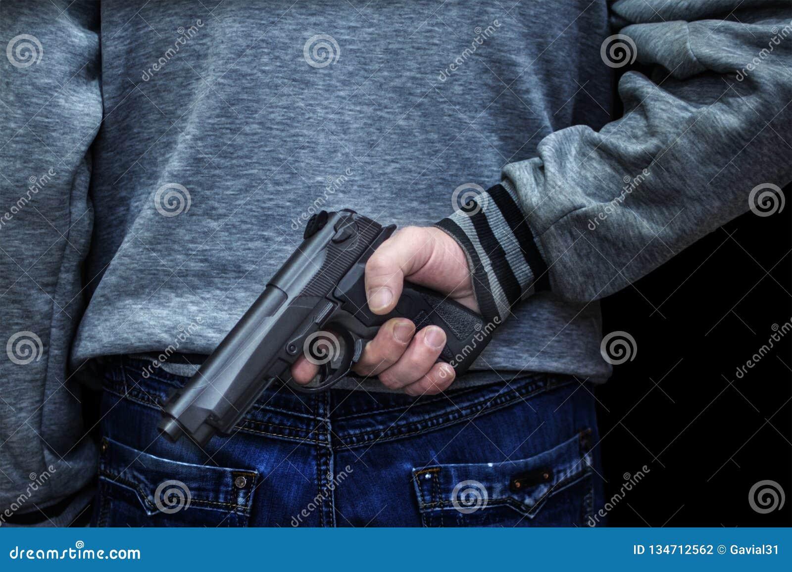 Uomo che tiene una pistola dietro il suo indietro contro un fondo nero concetto del pericolo, crimine