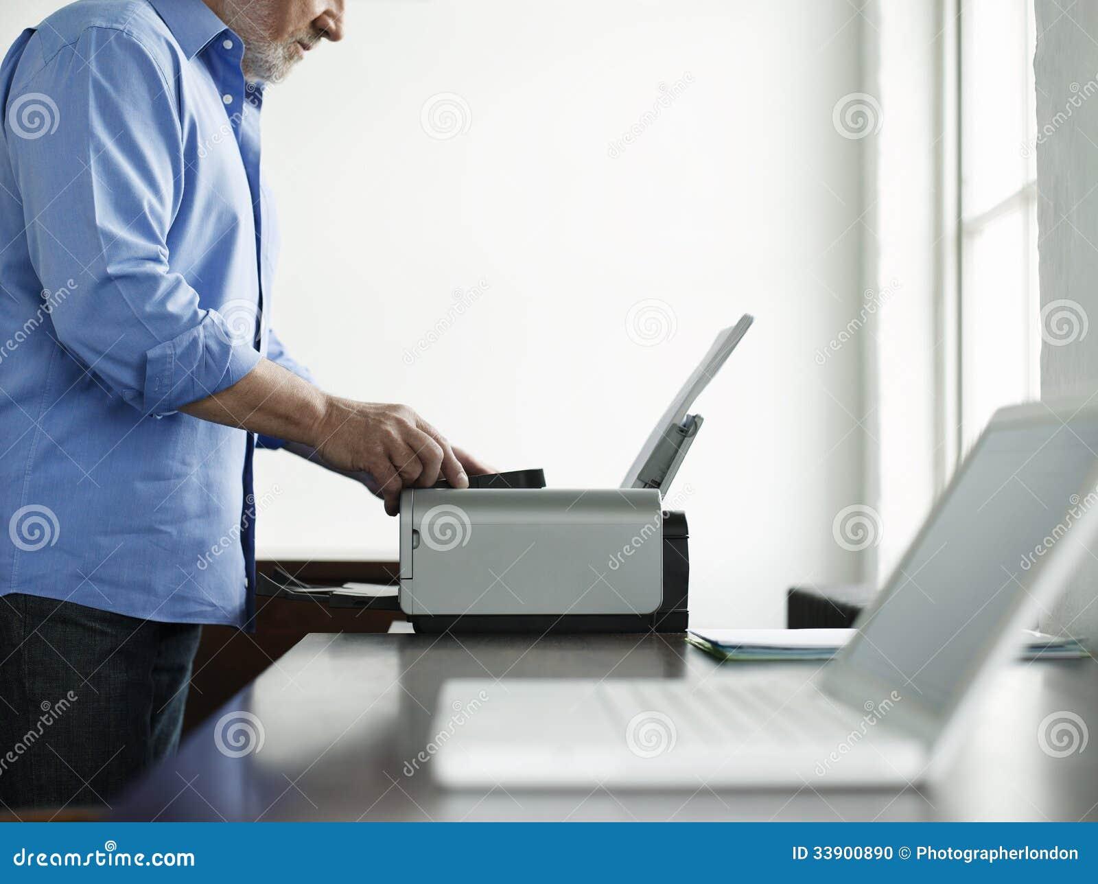 Uomo che utilizza stampatore At Study Table nella Camera
