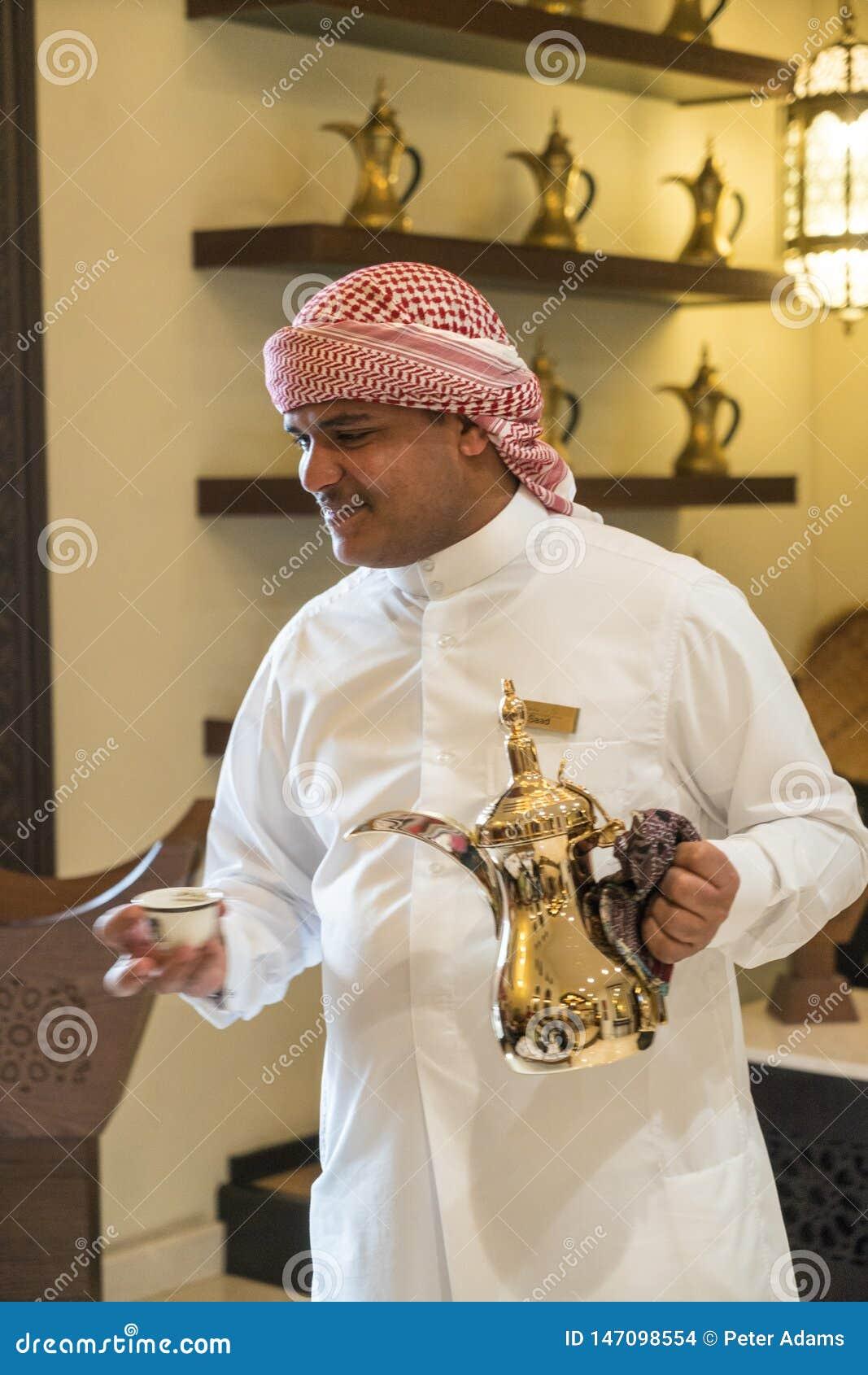 Uomo che versa caffè arabo da una caffettiera araba tradizionale di Dallah
