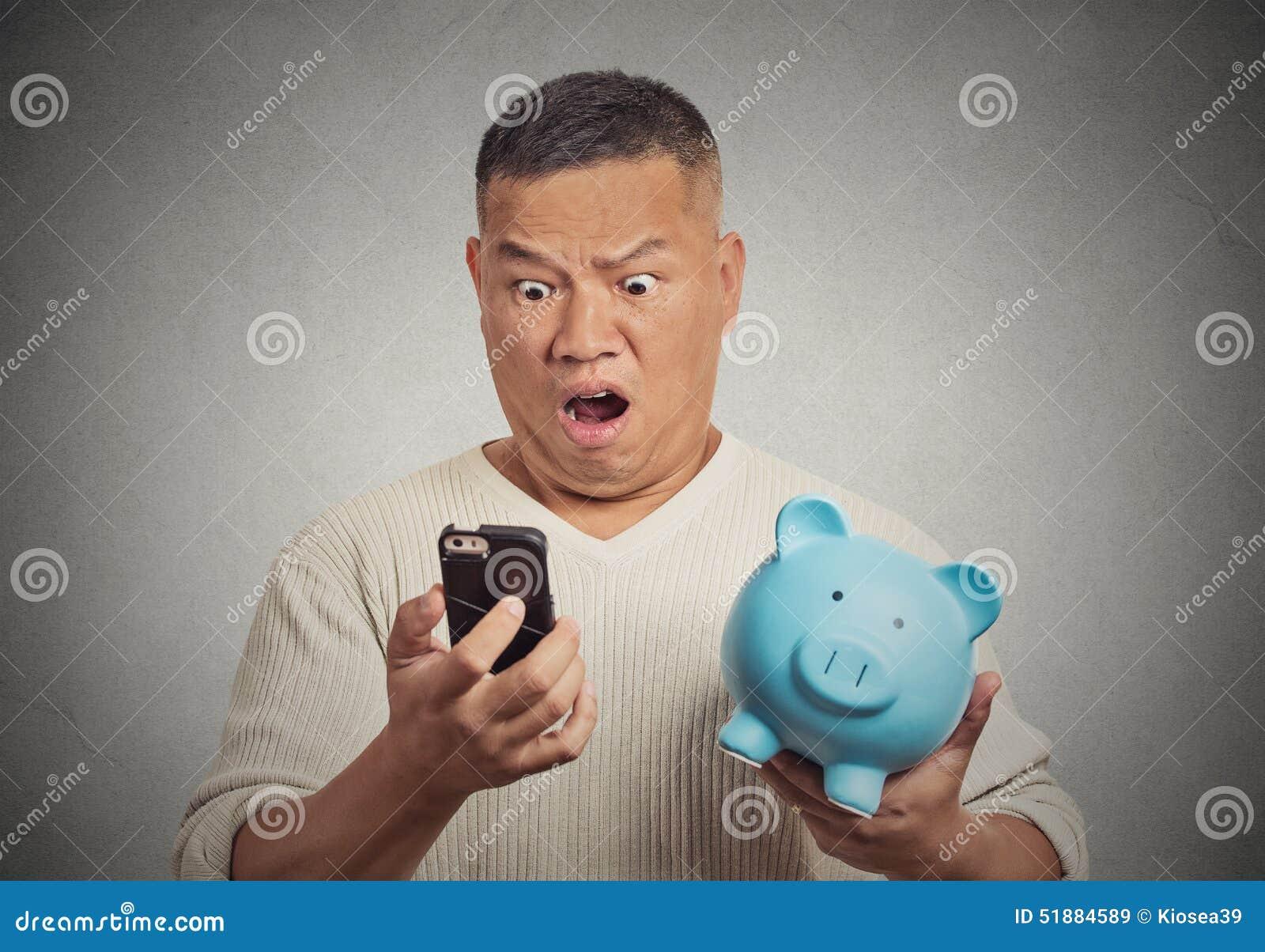 Uomo colpito che esamina il suo porcellino salvadanaio della tenuta dello Smart Phone