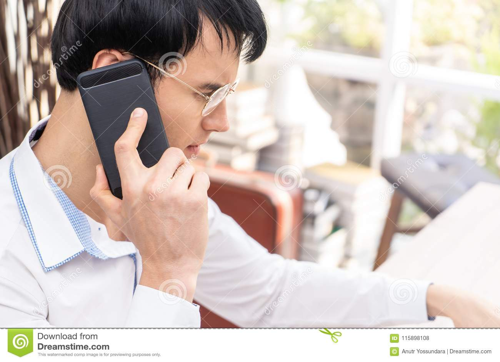 Uomo con i vetri facendo uso del colpo alto chiuso del telefono cellulare nero, bri